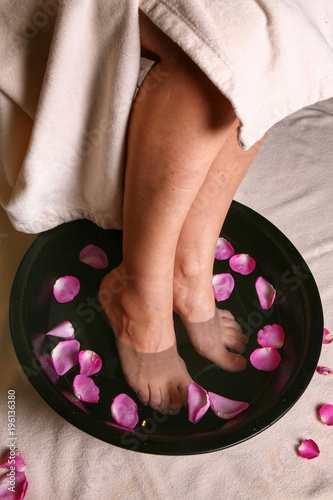 Fotobehang Pedicure Legs in a bowl of water with flower petals. SPA.