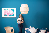 Beautiful young woman holding flowers standing in the cozy bedroom on the blue wall background at home