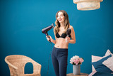 Portrait of a young woman standing with hairdryer on the blue wall background at home