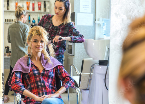 Foto op Canvas Kapsalon Working day inside the hair salon, hairdresser making hairstyle on a blonde woman.