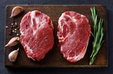 Fresh raw pork steaks, pepper, garlic, salt and rosemary on a dark wooden background. - 196138548
