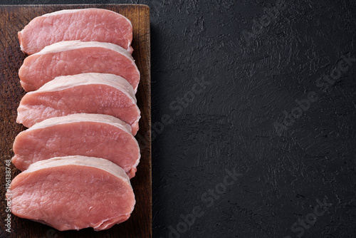 Raw sliced pork loin on a dark background. Fresh meat. - 196138748