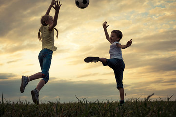 Happy young little boy and girl playing in the field  with soccer ball.