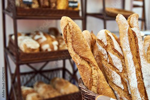 Fototapeta Bread baguettes in basket at baking shop
