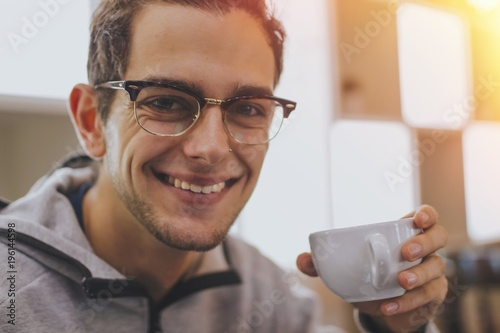 Poster portrait of trendy young man taking coffee