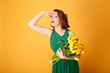 portrait of young woman with bouquet of yellow tulips looking away isolated on orange