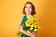 portrait of smiling woman with bouquet of yellow tulips isolated on orange