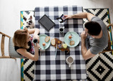 Loving couple sitting at a kitchen table, having a breakfast together - 196162595