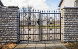 wrought iron fence gate and cut stone fence - 196169193