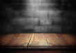Leinwanddruck Bild - Old wood table with blurred concrete block wall in dark room background.