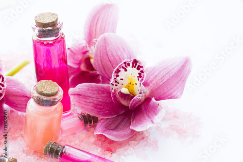 Foto op Canvas Spa Spa and wellness setting with orchid and rose sea salt and bottle with aroma oil on wooden white background closeup
