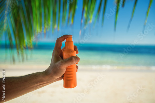 Bottle of sun protection lotion and palm leaf on the background