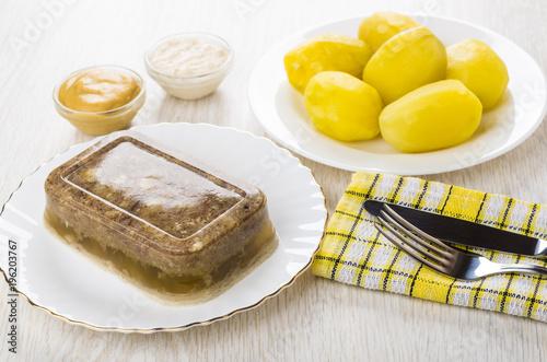Meat aspic in plate, knife, fork, mustard, horseradish, boiled potatoes © Evgeny