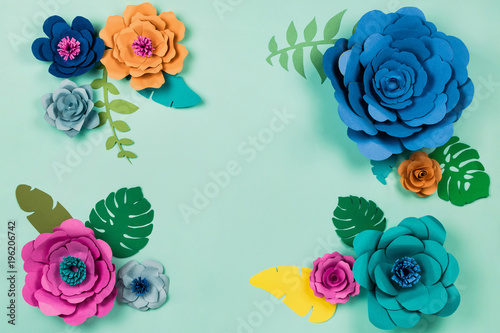 Beautiful floral spring or summer background. Papercraft flowers on blue background, top view, flat lay, copyspace