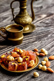 Oriental Arabian sweets with different nuts a cup of coffee. Eastern sweets. Traditional Turkish delight (Rahat lokum) on a wooden background. View from above. - 196208793