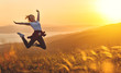 Happy woman jumping and enjoying life  at sunset in mountains.