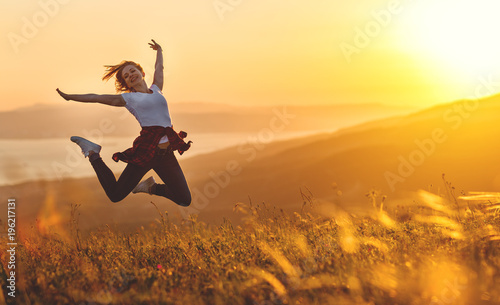 Happy woman jumping and enjoying life  at sunset in mountains. - 196217131