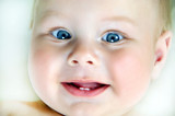 Close up of adorable 6 months old baby with first teeth looking at camera - 196220731