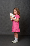 Girl in pink dress holding white stuffed toy - 196226310