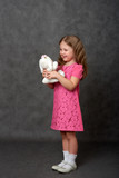 Girl in pink dress holding white stuffed toy - 196226329