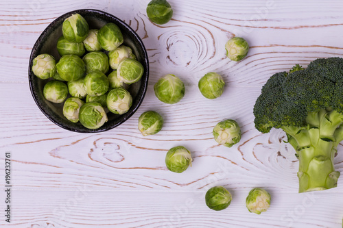 Deurstickers Brussel Fresh broccoli, Brussels sprouts in a bowl on a white wooden table - ecological products, healthy food. Flat lay
