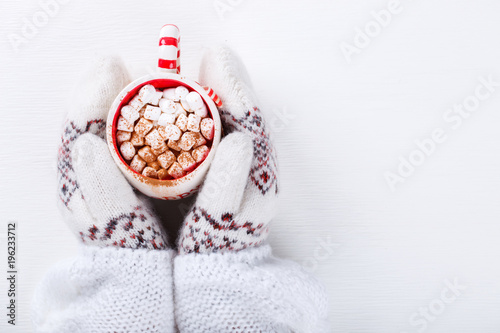 Fotobehang Chocolade Female hands holding hot chocolate with marshmallow and cinnamon. Warming holiday drink on a white background. Warm Christmas.CocoaTop view with Copy space