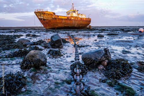 Fotobehang Schipbreuk Rusty old fishing vessel marooned at low tide on a mud bank a long anchor chain