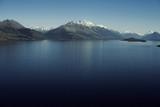 Paisaje de montañas con picos nevados. Las montañas se reflejan en un lago. Escena diurna, cielo azul y despejado. Nueva Zelanda.