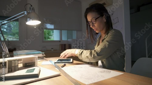 Wall mural Architect woman in office working on digital tablet