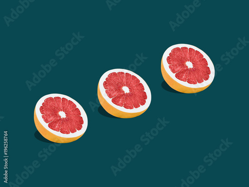 Plexiglas Pop Art Grapefruit in pop art style Three halves of ripe grapefruit are lying on a turquoise background Trendy photo with text space