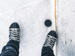 top down view of hockey puck and skates on ice