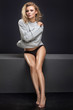 Sensual female model posing in fashionable sweater. Blonde beautiful woman with glamour makeup and long curly hair.