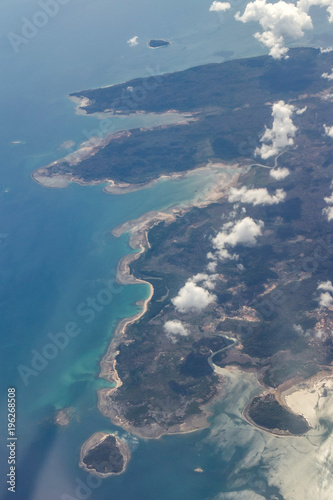 View from the airplane window to the clouds and the relief of the earth  - 196268508