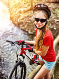 Cycling teen with ladies bikes in summer park. Woman road bike for running on nature. Teenager girl in helmet bicycle fording throught water. School trip. Sun flare background illumination. - 196298903