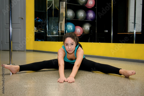 Attractive girl doing stretching fitness exercises