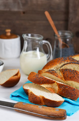 Bun, braided basket with poppy seeds and milk for breakfast. Food background. Good morning.