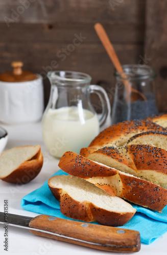 Staande foto Klaprozen Bun, braided basket with poppy seeds and milk for breakfast. Food background. Good morning.