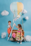 beautiful little kids pretending to fly on hot air balloon in cloudy sky