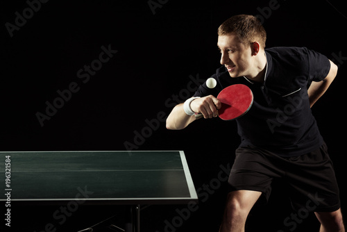 side view of young tennis player practicing in table tennis isolated on black - 196321584