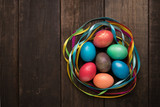 Easter eggs of different colors and bright ribbons on a wooden background. - 196324913