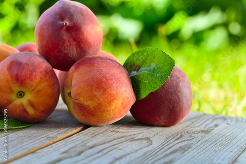 Juicy peaches on wooden table.