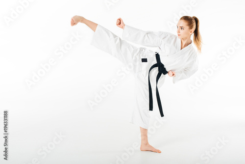 female karate fighter training kick isolated on white