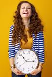 sad stylish woman isolated on yellow background with clock