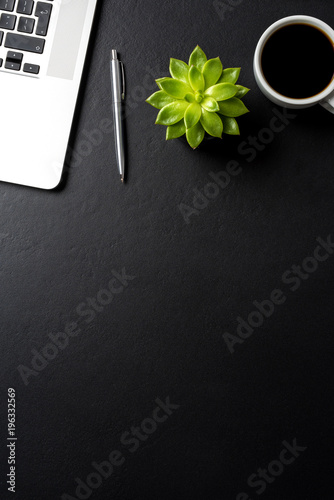 Elegant black office desktop with laptop and accessories. Business background