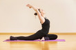 Younk woman is training yoga at kapotasana pose at gym background.
