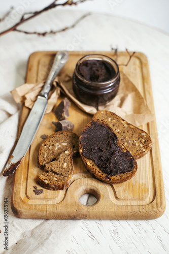 Wall mural Date fruit and chocolate spread on bread loaves for healthy breakfast on light background