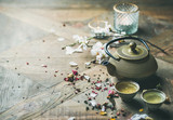 Traditional Asian tea ceremony arrangement. Iron teapot, cups, dried rose buds and candles over wooden table background, selective focus, copy space - 196335964