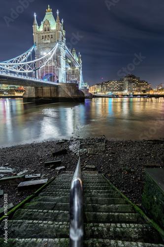 Fototapeta Stufen führen zum Ufer an der Themse mit Sicht auf die Tower Bridge in London am Abend