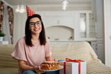 A girl in a cap alone with a cake with candles sitting on the sofa in the room. - 196341171