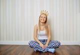 Funny blonde girl in pajamas with crown on her head smiling sits on the floor against a striped wall background. Young woman princess laughs in the room. - 196341581